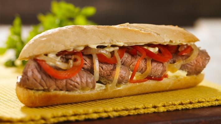 Sandwich tibio de carne, cebolla, morrones y queso con salsa de mayonesa
