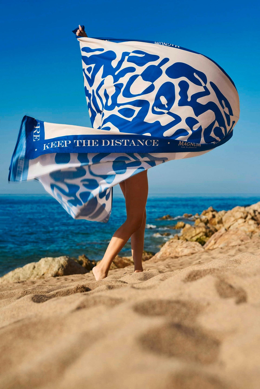 Mulher balançando uma toalha azul gigante na areia