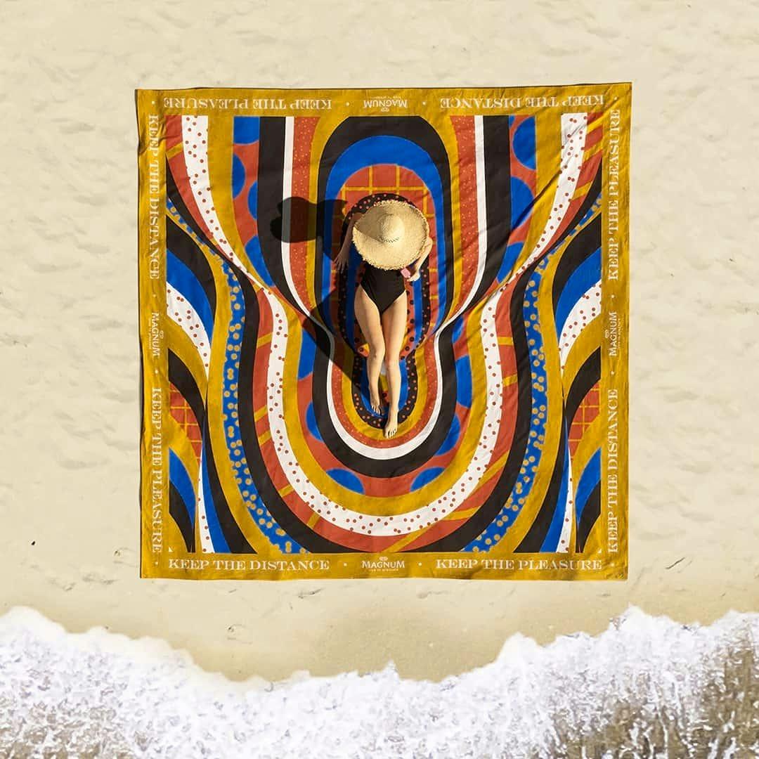 Mulher de maiô body preto deitada em uma toalha gigante estampada com formas que lembram ondas em várias cores quentes e bolinhas coloridas