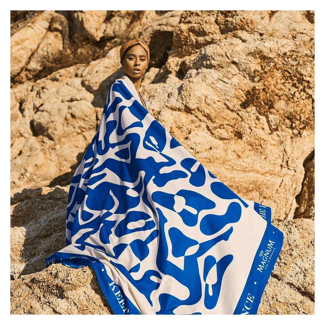 Mulher com uma bandana no cabelo sentada em um rochedo com o corpo inteiro coberto pela toalha gigante