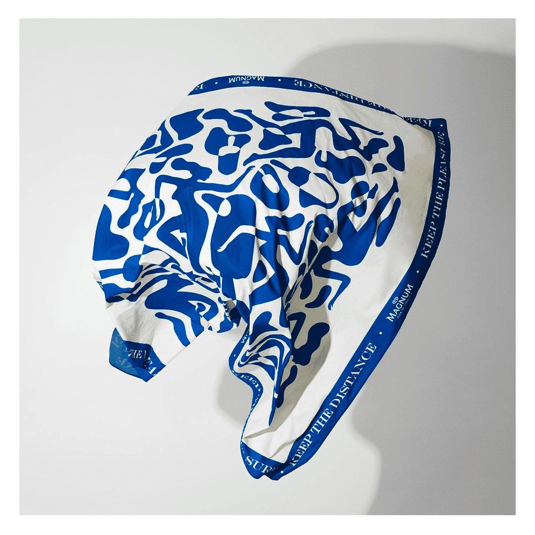 Toalha azul gigante jogada para cima contra uma parede branca
