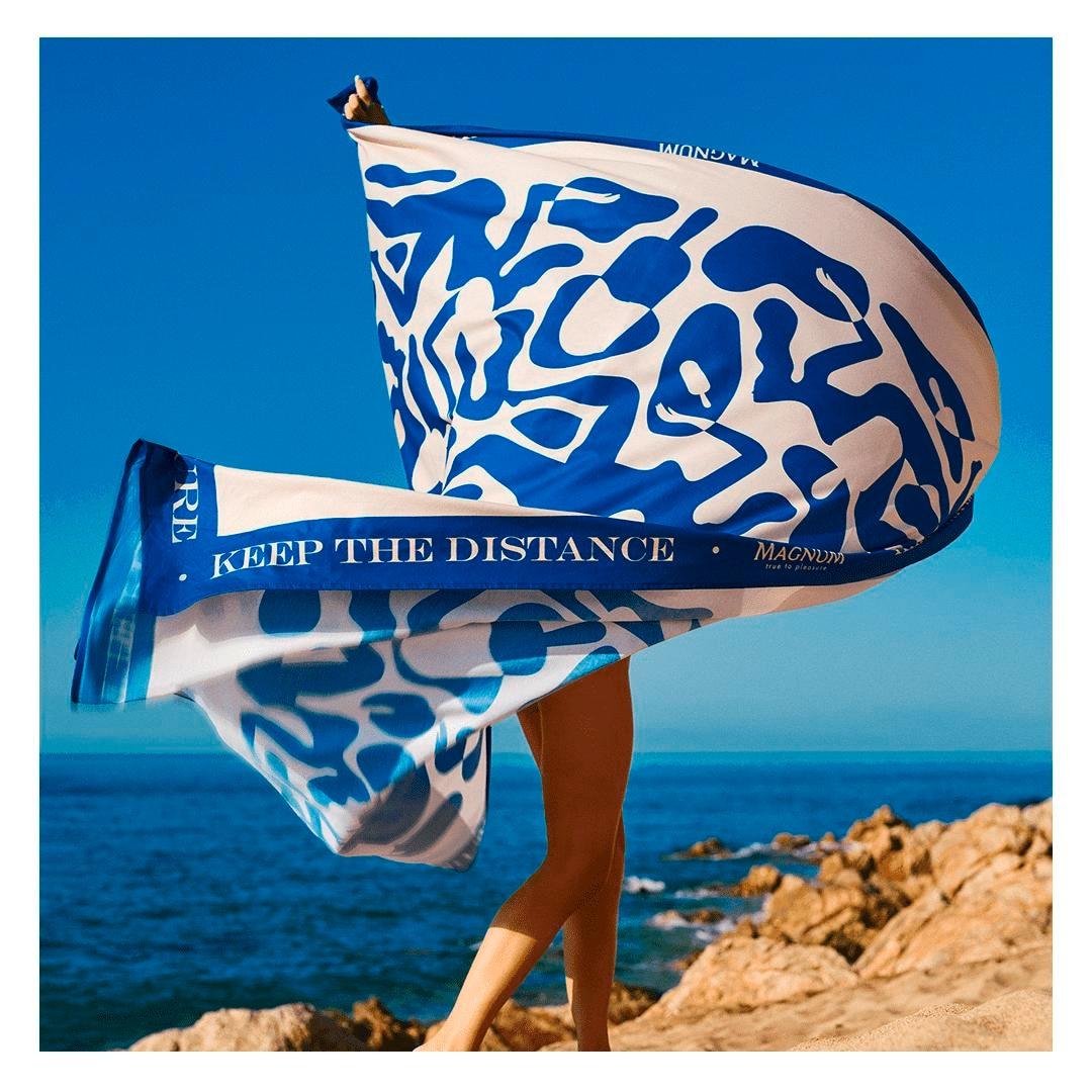 Mulher balançando uma toalha azul gigante em cima de pedras na praia