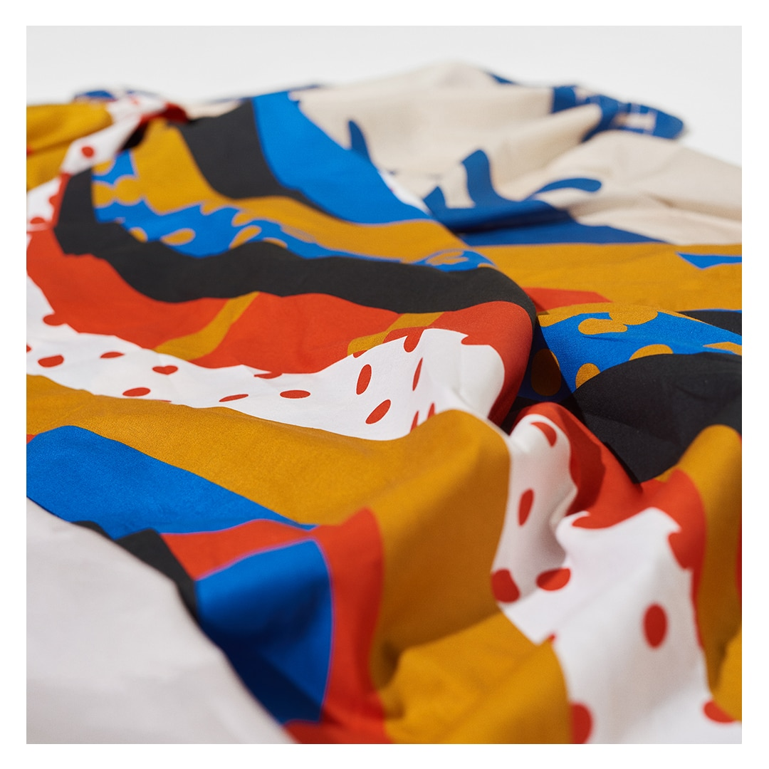 Foto aproximada de um tecido colorido com estampa em formato de ondas e bolinhas de cores quentes