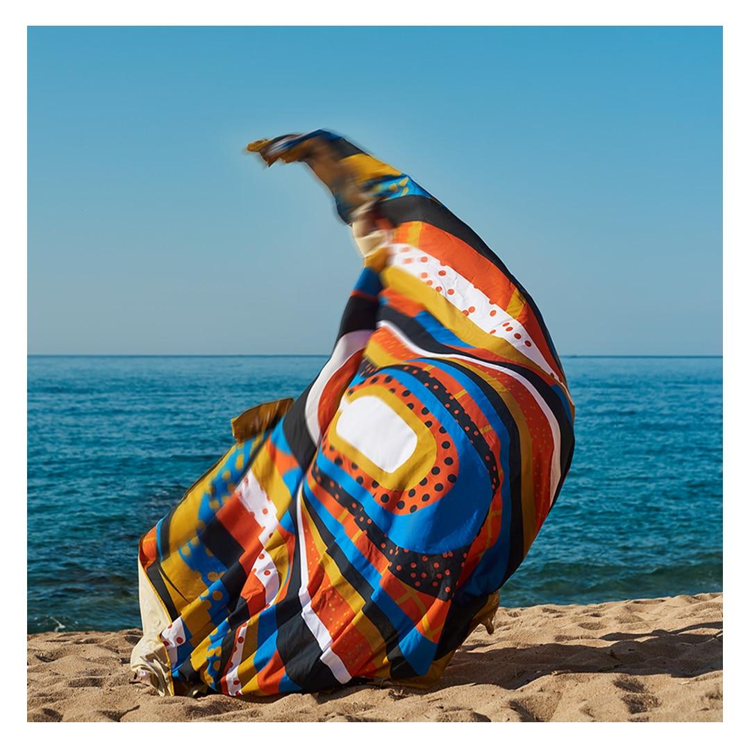 Toalha gigante jogada para cima na areia com o mar ao fundo, parecendo formar um casulo