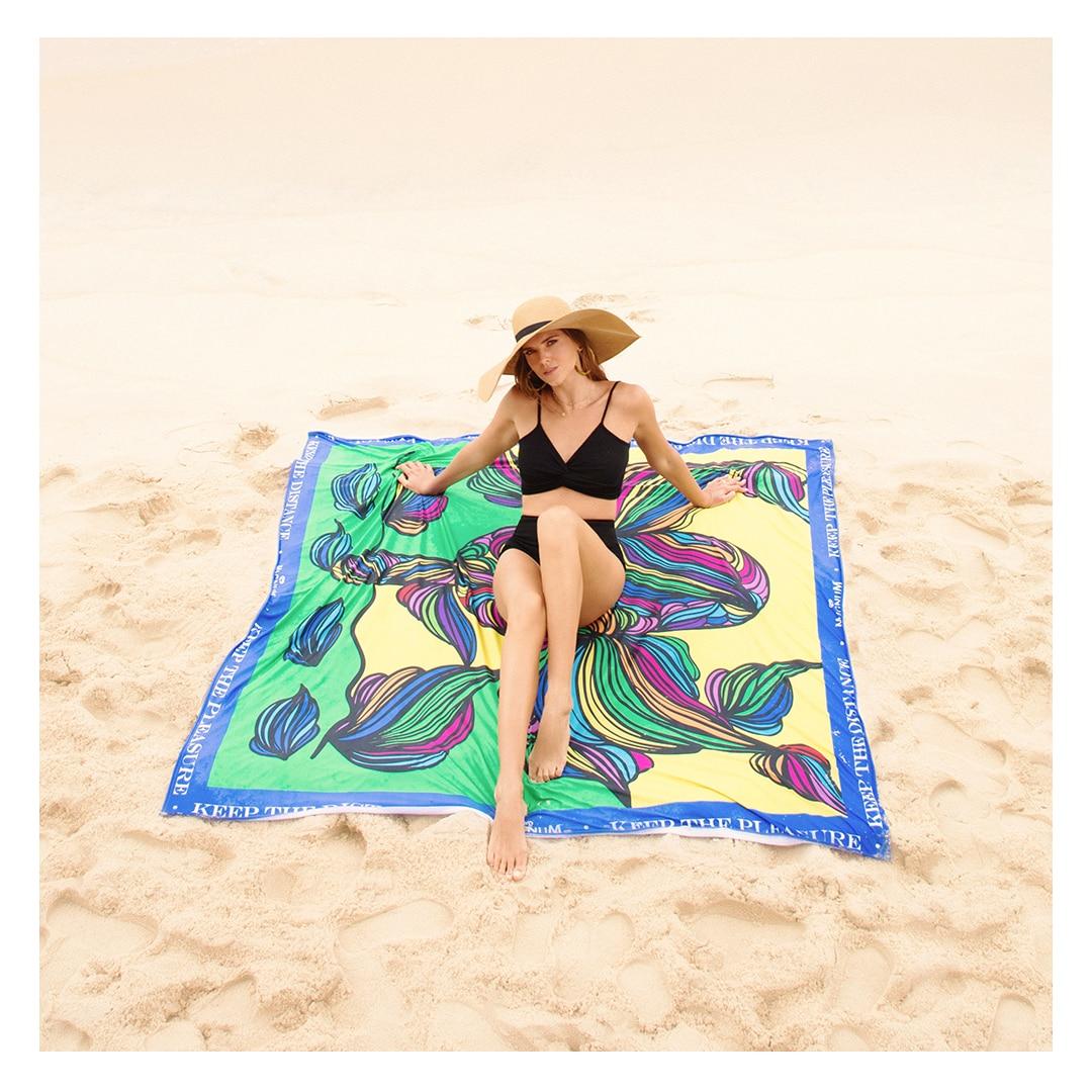Mulher de biquíni preto e chapéu de praia deitada, com espaço de sobra, na toalha gigante com estampas de folhas coloridas