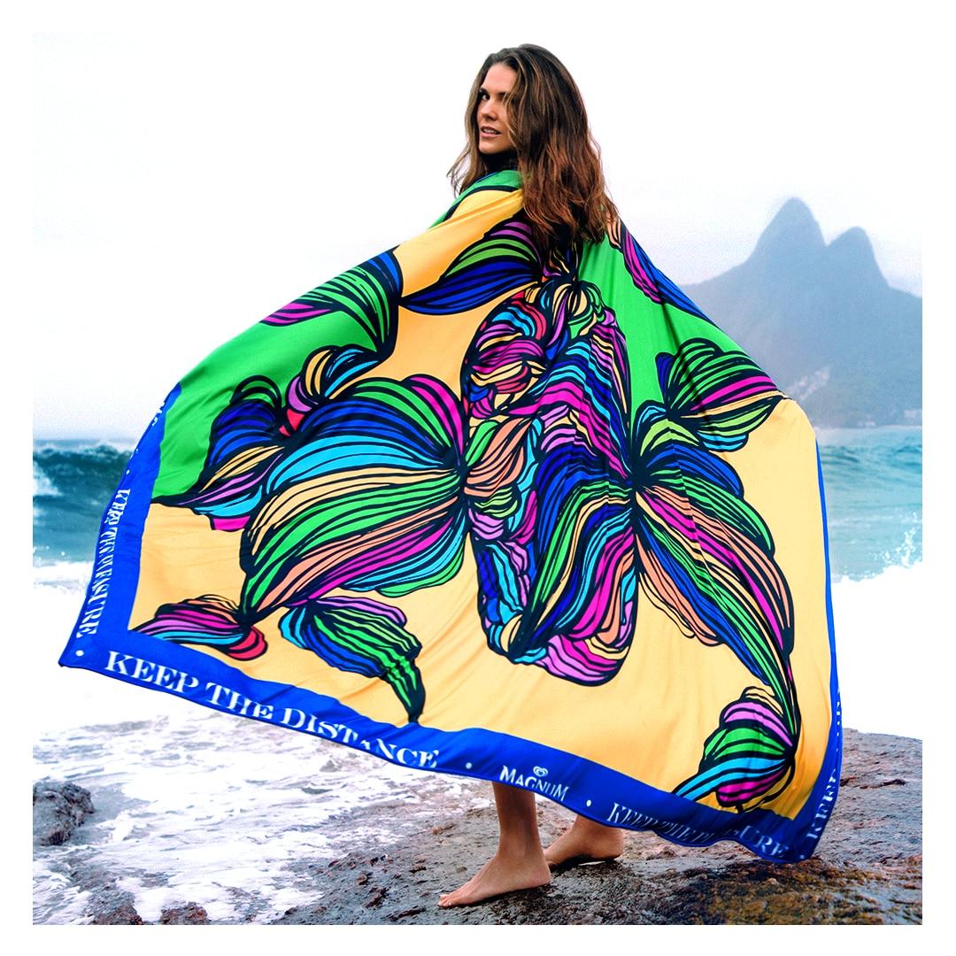 Mulher de pé nas pedras esticando os braços com a toalha gigante de Ciccy Halpern nas costas. Apenas seus pés estão visíveis