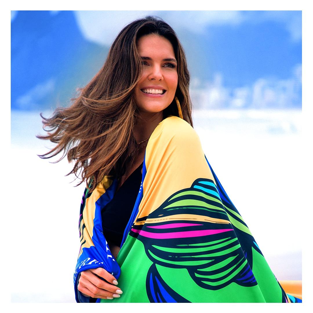 Mulher sorrindo embalada pela toalha gigante amarelo e verde