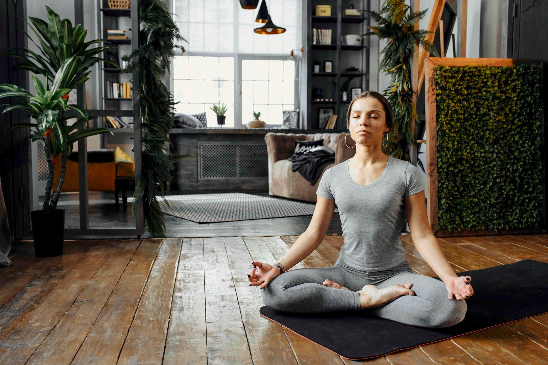 Uma mulher, sentada no chão de pernas cruzadas, pratica yoga de olhos fechados